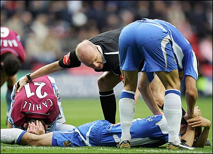 Referree Steve Bennett attends to Gary Cahill and Paul Scharner