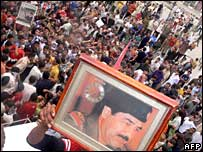 Demonstrators in Samarra wave portraits of Saddam Hussein after the verdict