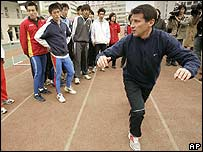Chairman of London's Olympic Organising Committee and former Olympic champion Sebastian Coe gives a lesson to students in Beijing