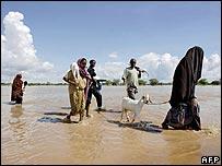 Displaced Somalis walk through the rising water in Dadaab, Kenya