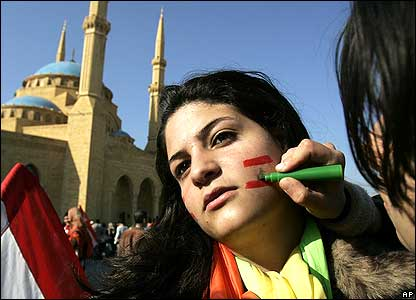 Hezbollah supporter paints Lebanese flag on her friend's face in front of Mohammed al-Amin Mosque.
