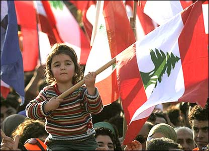 A child on her father's shoulders waves a Lebanese flag.