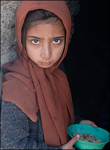 Huscha village, Herat province. Young hungry girl with stale bread soaked in water.
