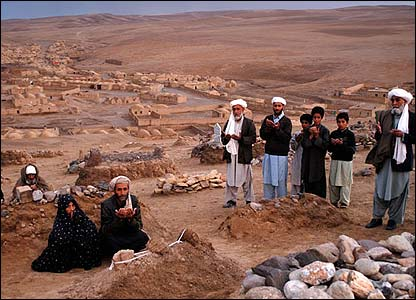 Saykamarak village. Cemetery. Local people praying at the graves of their dead babies. 