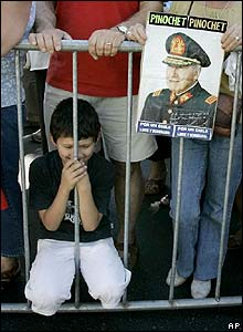 A young boy kneels among supporters of Gen Pinochet