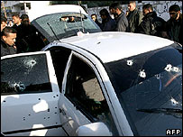 Palestinian security officers inspect the car hit in the attack