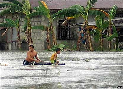 Man and boy on flooded street in Philippines