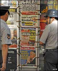Chilean soldiers look at a newsstand with papers reporting Pinochet's death