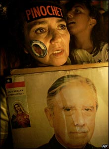 A woman holds a portrait of Gen Pinochet
