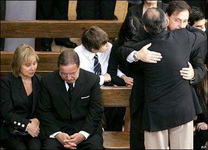 Members of Gen Pinochet's family comfort each other