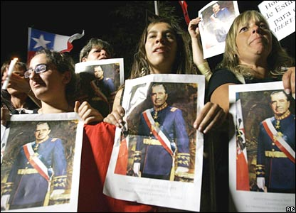Supporters of Gen Pinochet hold up his picture
