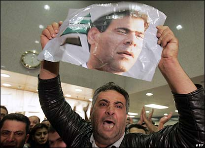 Supporters shout and wave pictures of Mr Gemayel
