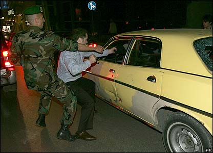 A man is held back as he tries to attack a Syrian taxi driver