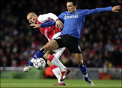 Freddie Ljungberg's forward progress is halted by Hamburg's Piotr Trochowski