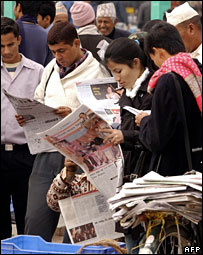 People read newspapers reporting on Nepalese government and Maoist rebels signing peace agreement in Kathmandu