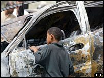 A child looks at a burnt-out car after a blast in Baghdad in July 2005