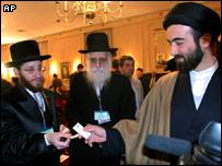 A rabbi gives his business card to a Muslim clergyman at the conference on the Holocaust, in Tehran, Iran