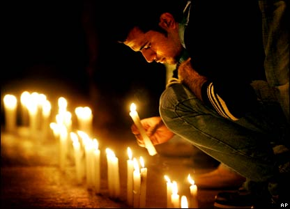 A mourner lights a candle at a vigil held at the scene where anti-Syrian Christian politician Pierre Gemayel was assassinated in eastern Beirut