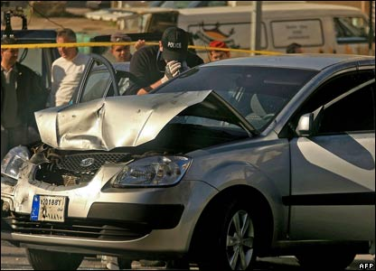 A Lebanese policeman from the forensic team takes video footage of the car