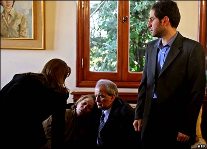 Communication Minister Marwan Hamadeh (C) comforts Joyce Tayan, mother of assassinated Lebanese Industry Minister Pierre Gemayel, as her younger son Sami stands next to them.