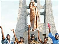 Ghanaians wave in front of a statue of the country's founder Kwame Nkrumah