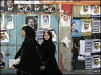 Bahraini women walk past posters of candidates running in Bahrain's upcoming parliamentary elections