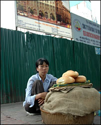 Pham Thi Diep selling bread in front of a new development of luxury offices