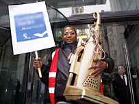 Cleaner holds a golden vacuum and a placard during the protest
