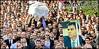 The coffin and a poster of assassinated Christian politician Pierre Gemayel are carried towards the family home in Bikfaya