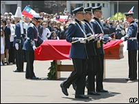 Soldiers remove the uniform and flag from Gen Pinochet's coffin