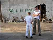 People in front of graffiti saying We'll be back in Mississippi after Hurricane Katrina