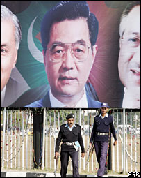 Pakistani policemen stand alert under a welcoming billboard showing pictures of Chinese President Hu Jintao (l) flanked by Pakistani President Pervez Musharraf (R