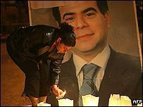 A mourner lights a candle at the site where Pierre Gemayel was assassinated