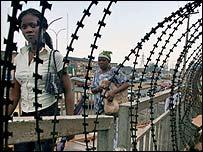 Women walk past barbed wire