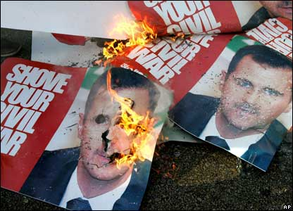 Posters of Syrian President Bashar al-Assad are set alight in Martyrs' Square, Beirut