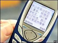 Полицейское СМС-сообщение на дисплее мобильного телефона китайца