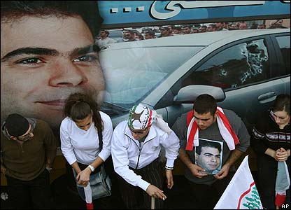 Lebanese mourners in Beirut sit in front of a poster of Pierre Gemayel