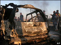 Palestinians look at a car hit by an Israeli strike, which targeted two suspected militants, 25 Nov 2006