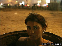 A young woman looks up from a hole leading to underground steam heaters where she and other teenagers and children are temporarily living