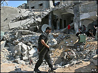 Armed Palestinian walks past a house bombed by Israeli forces