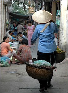 Woman wearing a traditional conical hat walking down a sidewalk
