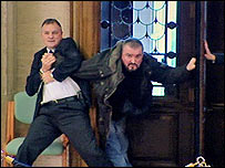 Michael Stone (right) being held at Stormont