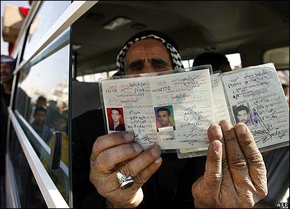 Woman with the ID cards of relatives killed in Baghdad
