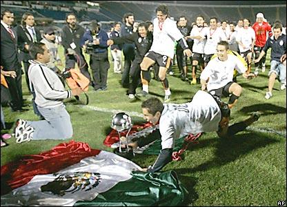 Los jugadores del Pachuca celebran, lanzándose sobre una bandera de México.