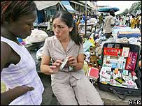 A woman sells Chinese medications at a market in Africa