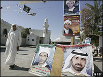 Bahraini man walks past election posters