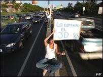 J�venes en una avenida de Caracas invitan a votar.