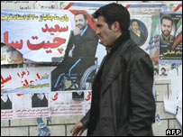 A man walks past election posters in Tehran