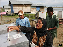 A woman votes at a polling station near Banda Aceh