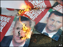 Posters of Syrian President Bashar Assad during a protest before the funeral of Pierre Gemayel